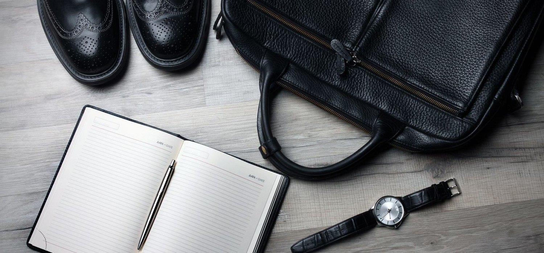 scarpe, orologio, borsa e blocco note aperto