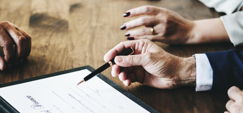 Signore con in mano una penna che firma un contratto