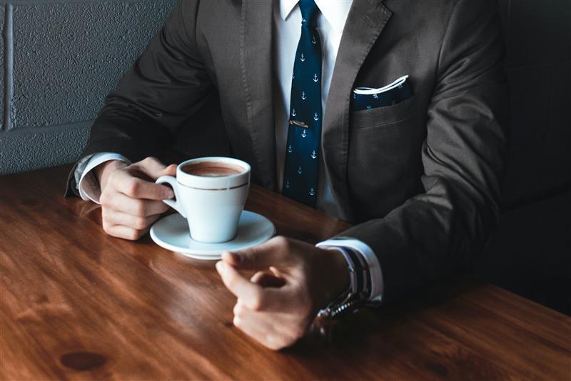 Uomo elegante che beve un cappuccino